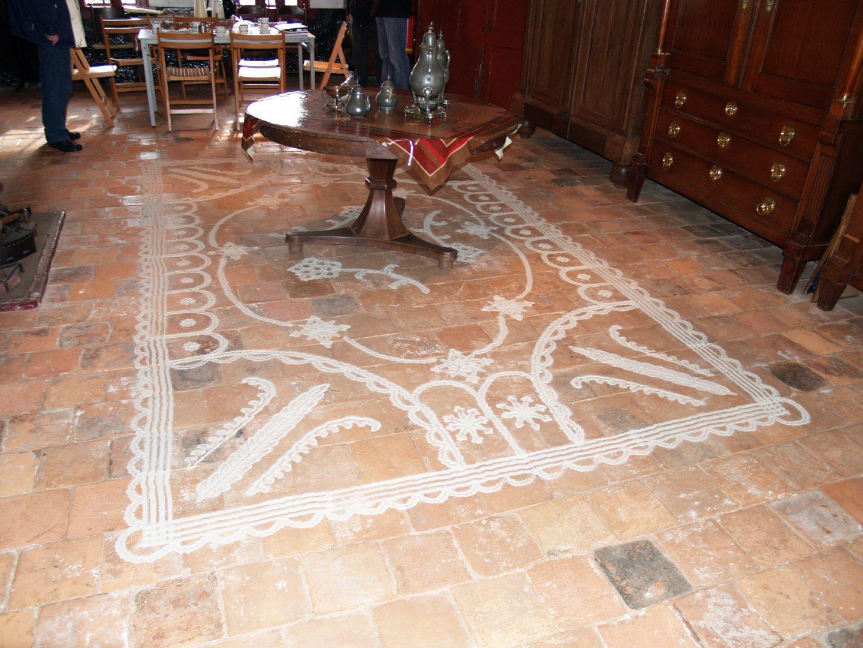 Met zand bracht de boerin een versiering aan op de kale vloer: een zandtapijt.